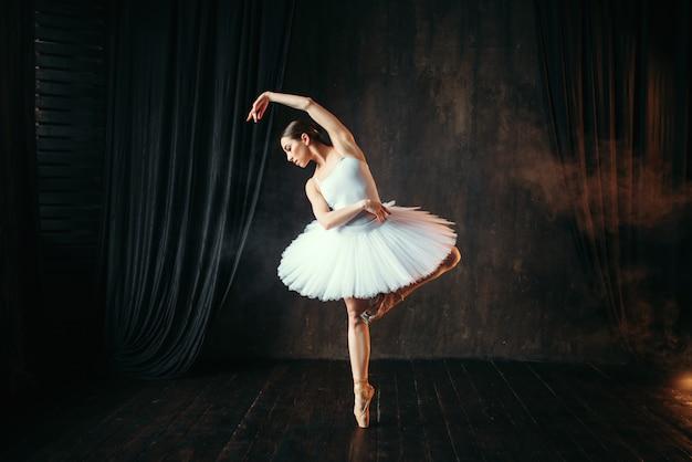 Sierlijke ballerina in witte jurk dansen op theatraal podium. klassieke balletdanseropleiding in de klas