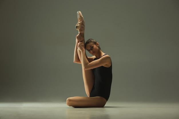 Sierlijke balletdanser of klassieke ballerina dansen geïsoleerd op grijze studio achtergrond. flexibiliteit en gratie tonen. het concept van dans, kunstenaar, hedendaags, beweging, actie en beweging.