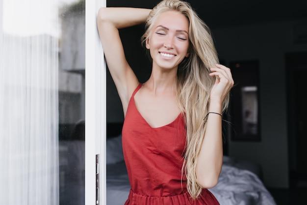 Sierlijke blanke vrouw in elegante pyjama poseren in de ochtend.