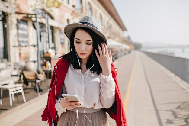 Sierlijke blanke vrouw kijken naar telefoon terwijl tijd buiten doorbrengen