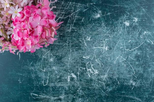 Sierlijke bloem in een kom, op de blauwe achtergrond.