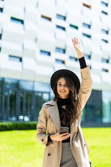 Sierlijke brunette vrouw in jas lopend onderaan de straat met telefoon in de hand.