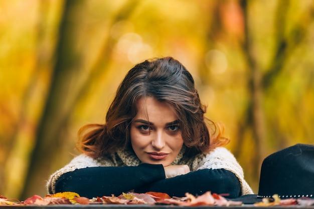 Sierlijke donkerharige vrouw kijkt naar de camera en leunt met haar hoofd op haar handen in de herfstbos.