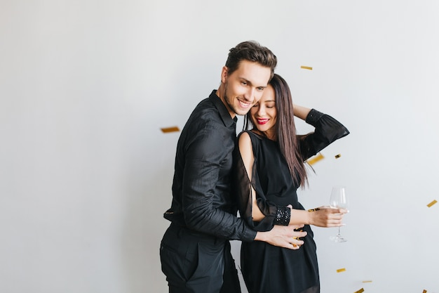 Sierlijke donkerharige vrouw leunt naar haar man met gesloten ogen en dromerige glimlach geïsoleerd op een witte achtergrond