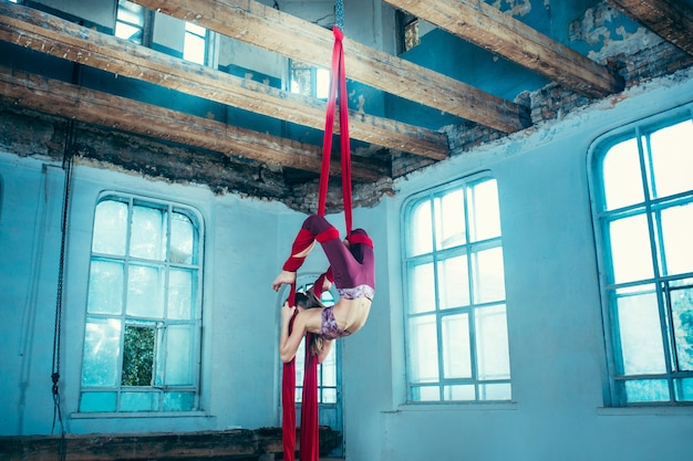 Sierlijke gymnast luchtoefening met rode stoffen op blauwe oude loft achtergrond. jong tiener kaukasisch geschikt meisje. het circus, acrobatische, acrobaat, artiest, sport, fitness, gymnastiekconcept