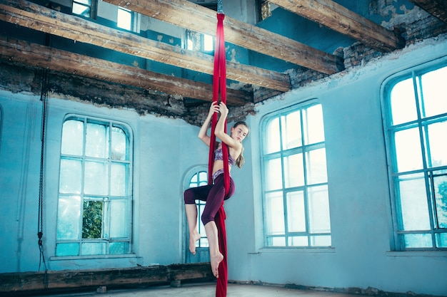 Sierlijke gymnast luchtoefening met rode stoffen op blauwe oude loft achtergrond.