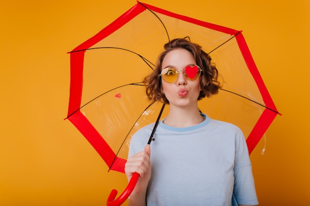 Sierlijke jonge vrouw in blauw shirt poseren met kussende gezichtsuitdrukking. studio shot van vrij vrouwelijk model met krullend haar gek rond tijdens fotoshoot met paraplu.