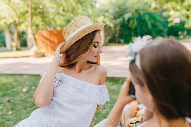 Sierlijke jonge vrouw in elegante vintage jurk poseren met gesloten ogen voor dochter. meisje dat met donker haar camera houdt en foto van moeder maakt