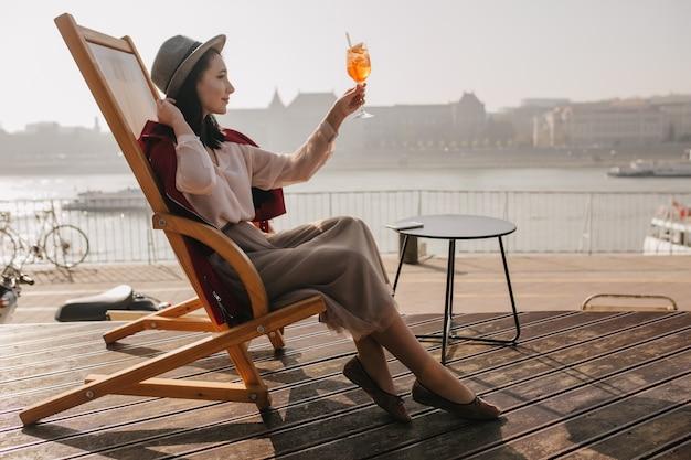 Sierlijke jonge vrouw in hoed zittend op chaise-longue op riviermuur