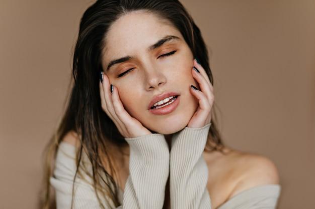 Sierlijke jonge vrouw met naakt make-up poseren met open mond. gelukkig kaukasisch vrouwelijk model dat over iets droomt.