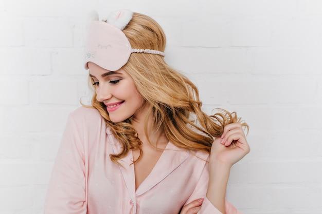 Sierlijke jonge vrouw speelt met glanzend krullend haar. verfijnd kaukasisch meisje in roze eyemask die in weekend ontspannen.
