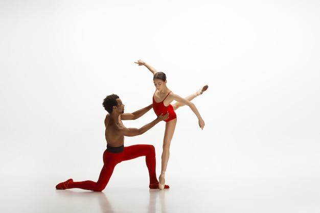 Sierlijke klassieke balletdansers dansen geïsoleerd op een witte muur. het concept van gratie, kunstenaar, beweging, actie en beweging.