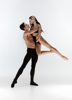 Sierlijke klassieke balletdansers dansen geïsoleerd op witte studio achtergrond.