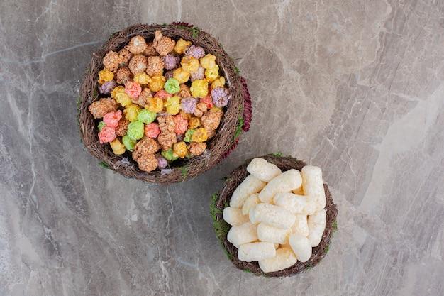 Sierlijke kommen met maïssnacks en met snoep beklede popcorns op marmer.