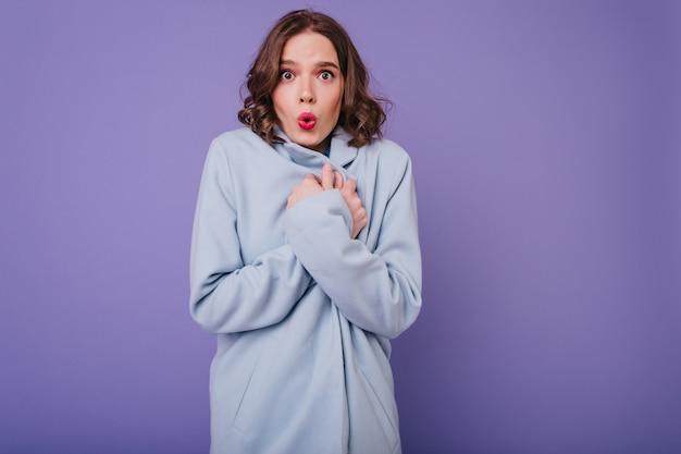 Sierlijke kortharige meisje met felle lippenstift poseren in koude dag. bruinharige vrouw in blauwe jas.