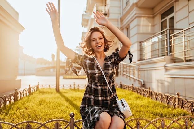 Sierlijke lachende dame met witte handtas handen zwaaien op straat. blij kaukasisch meisje dat in geruite kleding de herfstochtend geniet.