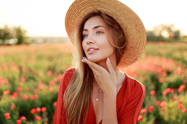 Sierlijke langharige vrouw die op horizon kijkt, genietend van vrijheid. verleidelijke meisje poseren op papavergebied. warm zonsonderganglicht.