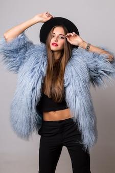Sierlijke magere vrouw in stijlvolle pluizige blauwe winterjas en zwarte hoed poseren op helder grijze muur.