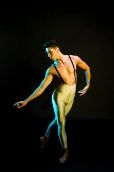 Sierlijke mannelijke balletdanser presteren in de schijnwerpers
