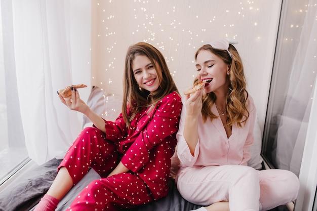 Sierlijke meisjes die op bed zitten en pizza eten. vrij kaukasische dames die weekendochtend doorbrengen in slaapkamer met fastfood.