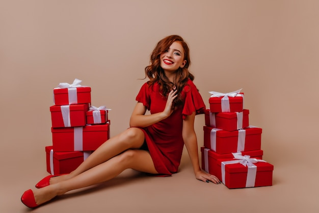 Sierlijke roodharige jonge vrouw koelen op nieuwjaarsfeest. tevreden gember meisje zit in de buurt van kerstcadeautjes.