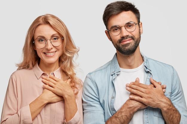 Sierlijke vrolijke positieve jonge vrouw en man hebben tevreden uitdrukkingen, houd beide handen op het hart