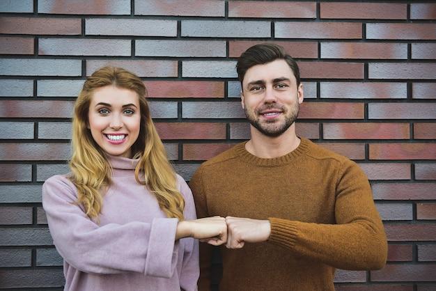 Sierlijke vrolijke positieve jonge vrouw en man hebben tevreden uitdrukkingen, houden beide handen op het hart, voelen zich dankbaar voor gasten, zijn in hoge geest, staan tegen een wit oppervlak.