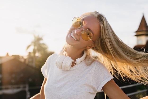 Sierlijke vrouw in gele zonnebril genieten van het leven in zomeravond.