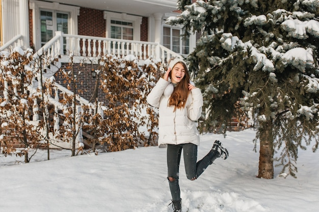 Sierlijke vrouw in gescheurde spijkerbroek dansen op de besneeuwde straat in winterdag. openluchtportret van verfijnde europese vrouw in witte jas die rond in de tuin naast sparren ronddwaalt.