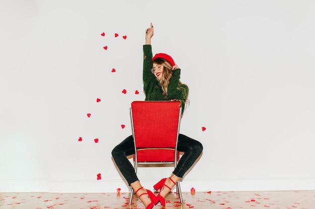 Sierlijke vrouw in rode schoenen met hoge hakken, zittend op een stoel en lachen