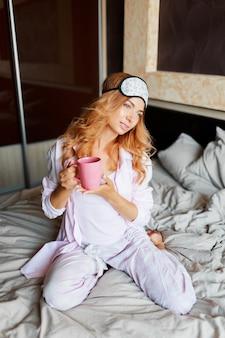 Sierlijke vrouw met openhartige glimlach poseren in oogmasker in haar slaapkamer en het drinken van hete thee.