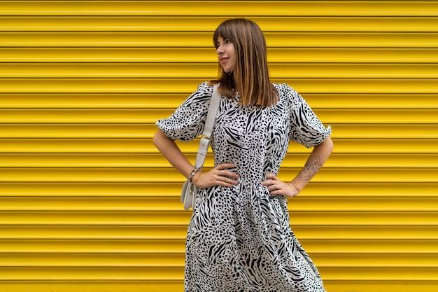 Sierlijke vrouw met tatoeage bij de hand poseren over gele stedelijke muur.