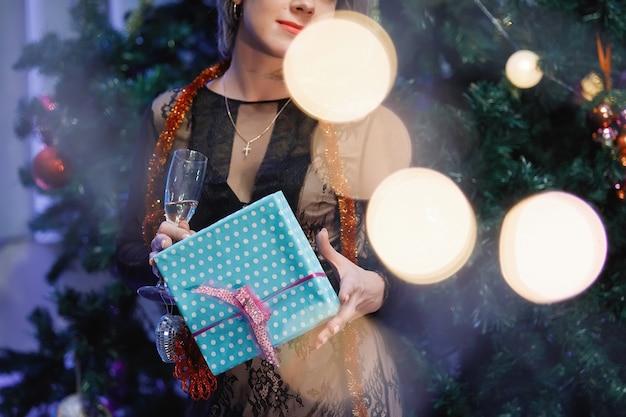 Sierlijke vrouw verheugt zich met een geschenkdoos in de buurt van een kerstboom. een vrouw lacht, glimlacht, poseert. speciale vintage ruis- en graanfilter, wazige lichten.