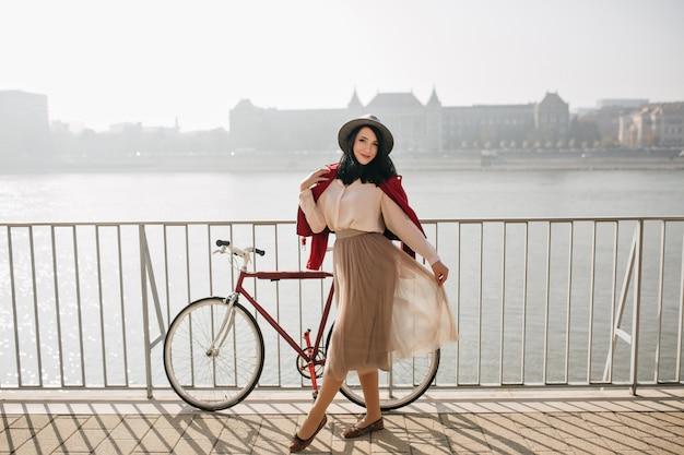 Sierlijke vrouwelijke model poseren met benen gekruist op riviermuur