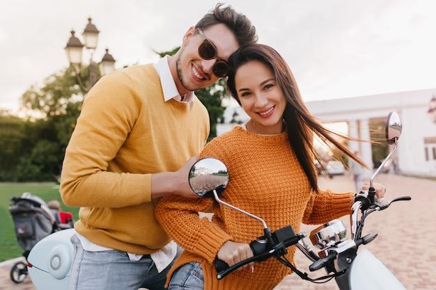 Sierlijke vrouwelijke modellen in gebreide kleding poseren met schattige glimlach op de fiets