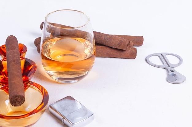 Sigaar, asbak, sigarettenschaar, witte betonnen tafel van lichter whiskyglas.
