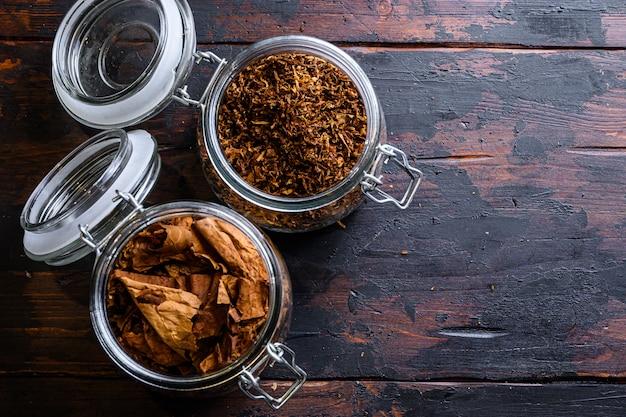 Sigaar en stapel tabaksbladeren van gedroogde tabak in glazen potten op rustieke houten donkere tabel bovenaanzicht ruimte voor tekst