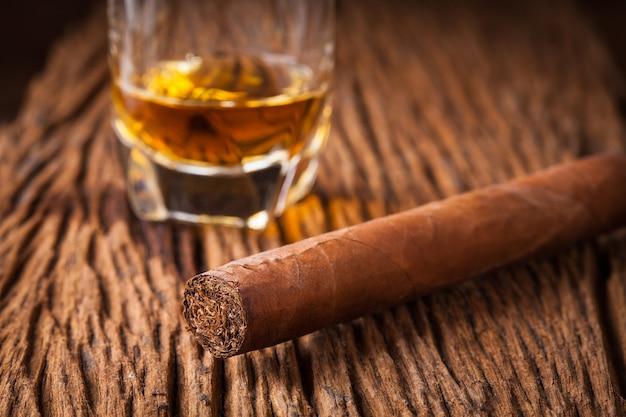 Sigaar en whisky op oude houten tafel