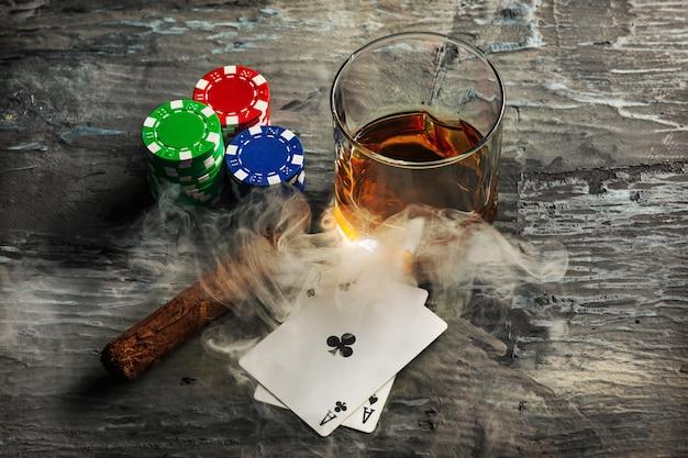 Sigaar, fiches om te gokken, drank en speelkaarten