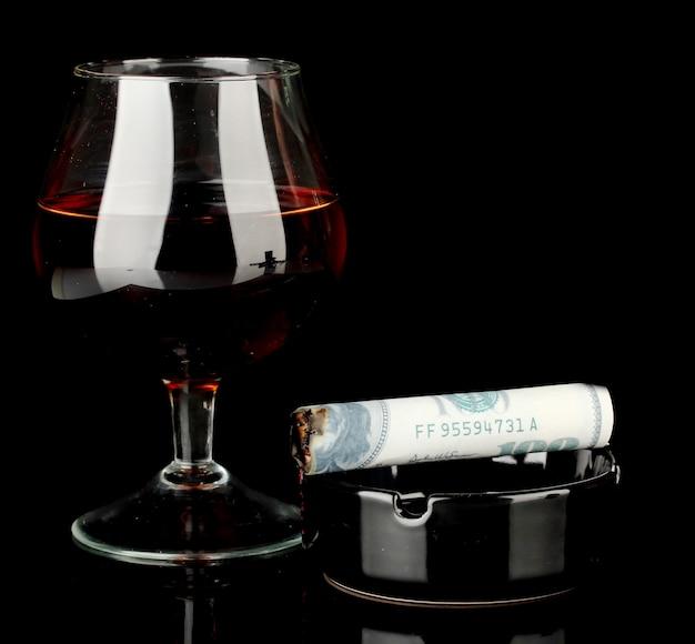 Sigaar van het 100-dollarbiljet en een asbak en een glas cognac geïsoleerd op zwart