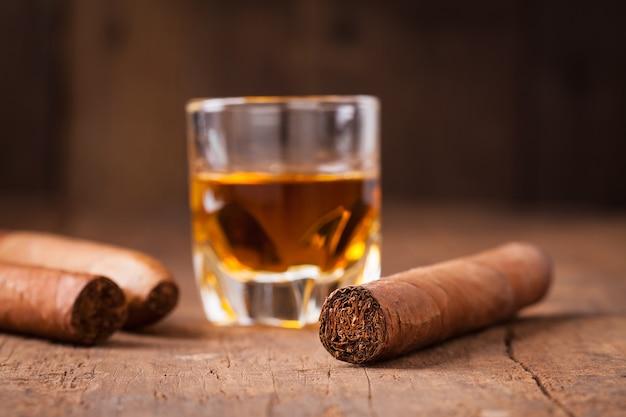 Sigaren en whisky op oude houten tafel