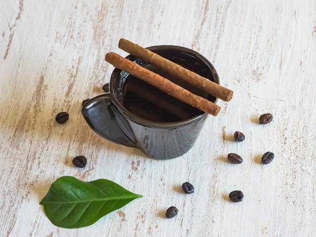 Sigaren op een kopje zwarte koffie met koffiebonen.
