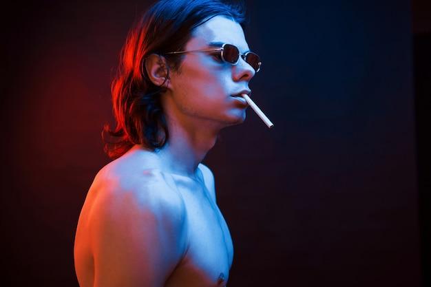Sigaret roken. studio opname in donkere studio met neonlicht. portret van ernstige man