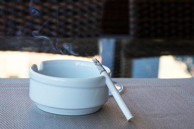 Sigaretten in asbak bij rookruimte. sigaretten en tabak liggen in keramische asbak op de buitentafel. werelddag zonder tabak op 31 mei. selectieve aandacht. gezondheidszorg en object concept.