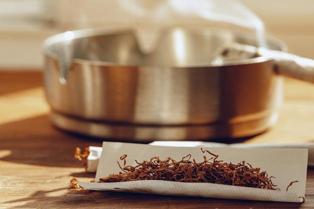 Sigarettenpapier en stapel tabak op houten tafel