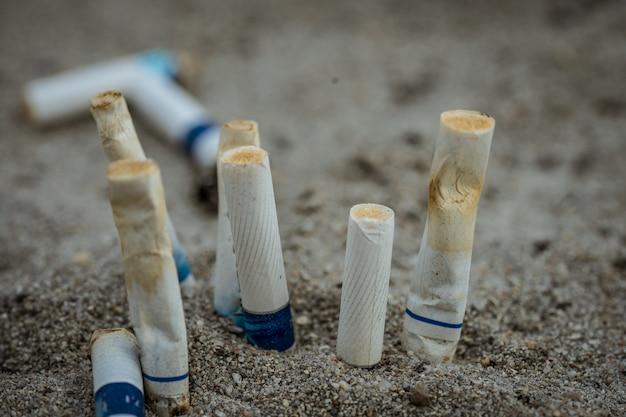 Sigarettenpeuken na gebruik en daarna achtergelaten op het zand