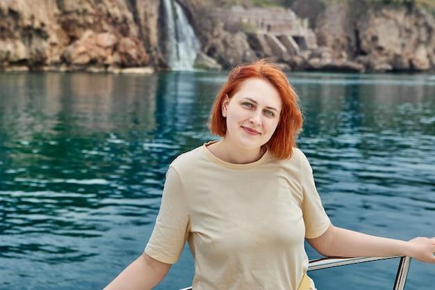 Sightseeing zeetour op jacht jonge europese vrouw poseren voor fotograaf