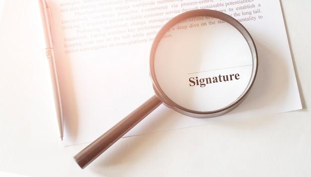 Signaure lijn in contract met pen en vergrootglas