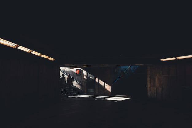 Silhoette van twee mensen die een donker schaduwrijk ondergronds gebouw binnengaan