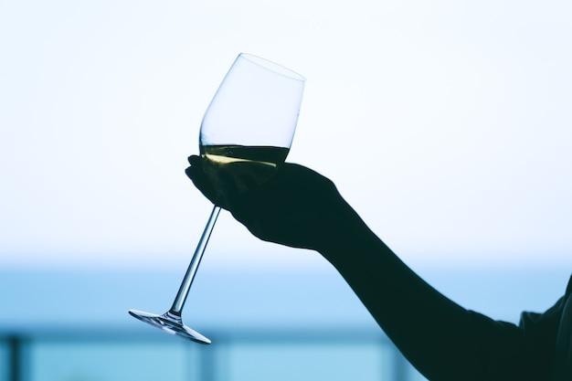 Silhouet afbeelding van een vrouw hand met een glas wijn met wazig zee achtergrond